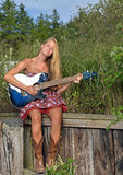 Beautiful female guitar player outdoors. Stunning and sexy young woman in strapless dress and cowboy boots outdoors playing a blue guitar - music series Stock Photography