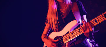 Beautiful female guitarist performing in nightclub Stock Photography