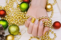 Beautiful female hand with beige nail design. Christmas manicure. Beautiful female hand with beige nail design. Christmas manicure with golden accent Stock Photos