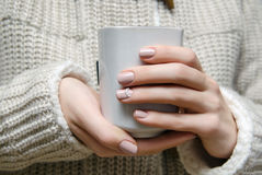 Beautiful female hand with beige nail design. Royalty Free Stock Images