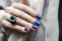 Beautiful female hand with blue nail design. Royalty Free Stock Images