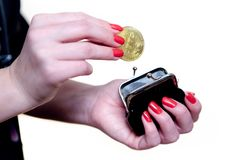 A beautiful female hand hides the bitcoin in a purse. Stock Images