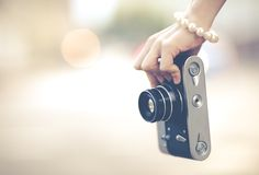 Beautiful female hand hold the camera of vintage close up. Colorful hipster photo Royalty Free Stock Image