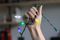 Beautiful female hand with manicure holds a garland of light bulbs. Deep dark green nail polish. Beautiful female hand with manicure holds a garland of light royalty free stock image