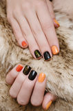 Beautiful female hand with orange and black nail art royalty free stock images