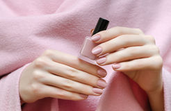Beautiful female hand with warm pink nail design. Holding nail lacquer bottle Royalty Free Stock Photography