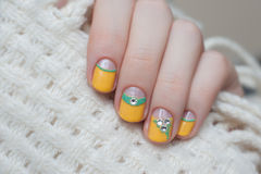 Beautiful female hand with yellow nail design. Royalty Free Stock Photos