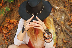 Beautiful female hands with boho chic dreamcatcher bracelets and black leather hat. White manicure, no face, indie style, autumn outdoor stock image