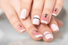 Beautiful female hands with a fashionable manicure. Geometric design of nails. Photo closeup Royalty Free Stock Images