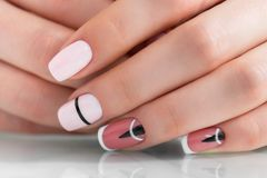 Beautiful female hands with a fashionable manicure. Geometric design of nails. Photo closeup royalty free stock image
