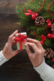 Beautiful female hands holding a Christmas present in box with red bow. Stock Photo