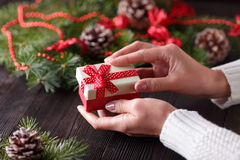 Beautiful female hands holding a Christmas present in box with red bow. Stock Images