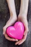 Beautiful female hands holding pink plastic heart. Over old wooden table stock images