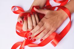 Beautiful female hands holding red ribbon stock images