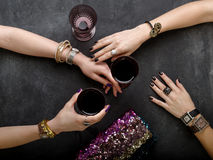Beautiful female hands with jewelry at the table with glasses of Royalty Free Stock Photo