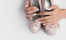 Beautiful female hands with long nails and french manicure on wedding shoes Stock Photo
