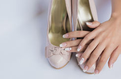 Beautiful female hands with long nails and french manicure on wedding shoes with a bow on a white background Royalty Free Stock Photo