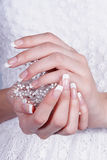 Beautiful female hands with manicure. Against a white dress Royalty Free Stock Photo