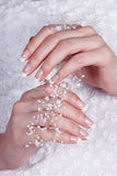 Beautiful female hands with manicure. Against a white dress Stock Photography