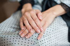 Beautiful female hands with manicure against a dress Stock Image