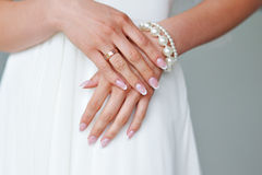 Beautiful female hands with manicure against a white dress Stock Images