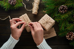 Beautiful female hands are packed Christmas gift in brown kraft paper. Royalty Free Stock Images