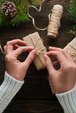 Beautiful female hands are packed Christmas gift in brown kraft paper. Stock Photography