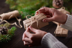 Beautiful female hands are packed Christmas gift in brown kraft paper. Stock Image