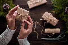 Beautiful female hands are packed Christmas gift in brown kraft paper. Royalty Free Stock Photo