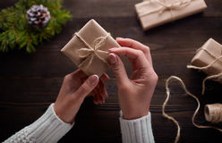 Beautiful female hands are packed Christmas gift in brown kraft paper. Stock Photos
