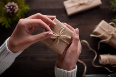 Beautiful female hands are packed Christmas gift in brown kraft paper. Royalty Free Stock Image