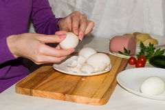 Beautiful female hands peeling a boiled egg from the rind. For cooking salad royalty free stock photos