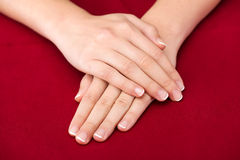 Beautiful Female Hands on red background Stock Photo