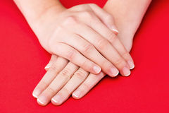 Beautiful Female Hands on red background Royalty Free Stock Photo