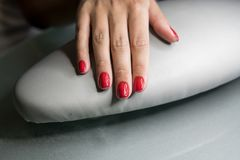 Beautiful female hands with red nails in beauty nail salon. Beautiful female nails and manicure. stock image