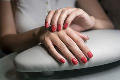 Beautiful female hands with red nails in beauty nail salon. Beautiful female nails and manicure. Beautiful female hands with red nails in beauty nail salon royalty free stock photo