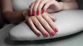 Beautiful female hands with red nails in beauty nail salon. Beautiful female nails and manicure. stock footage
