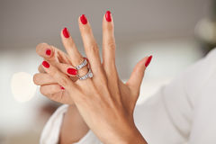 Beautiful female hands with red nails and elegant diamond rings. Royalty Free Stock Photo
