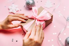 Beautiful female hands with trendy manicure holding gift box on festive christmas background. Close up photo of Christmas gift Stock Photo