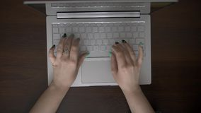 Beautiful female hands typing on laptop keyboard. Beautiful female hands with a manicure and wearing a ring, typing text on the laptop keyboard. A dark stock video footage
