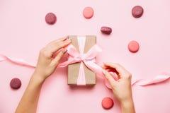 Beautiful female hands vith fashion manicure tie a bow on gift box. Beautiful female hands vith fashion manicure tie a bow on gift box on pink table vith royalty free stock photo