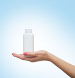 Beautiful female hands with a white bottle Royalty Free Stock Photography