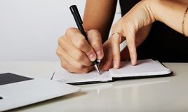 Beautiful Female hands write pen in a notebook of tasks and goals to work on a wooden table.The hands of a business. Woman writing on a notepad with a pen stock photos
