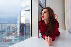 Beautiful female having fun relaxing looking out the window, portrait Stock Image
