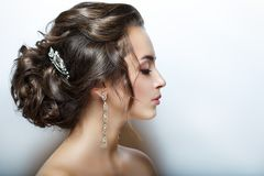 Beautiful female head. Profile. Closeup portrait of. Perfect skin, beautiful hair and makeup. Large and bright decorations. Horizontal photo. Light grey royalty free stock photo