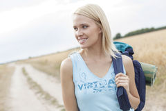 Beautiful female hiker with backpack looking away while standing on field Royalty Free Stock Photos