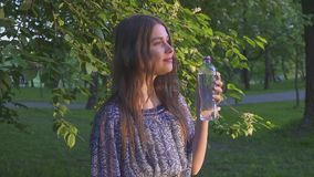 Beautiful female hiker drinking water in forest at sunset. A girl in a dress drinks cool water from a plastic bottle. stock video