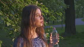Beautiful female hiker drinking water in forest at sunset. A girl in a dress drinks cool water from a plastic bottle. stock footage