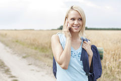 Beautiful female hiker using mobile phone on field Stock Photography