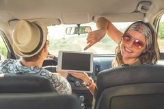 Beautiful female holding digital tablet device and sitting in car with her boyfriend. Travel and technology concepts. royalty free stock image
